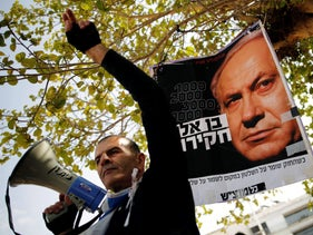 Protesters in Tel Aviv hold signs during a rally calling upon Prime Minister Benjamin Netanyahu to step down, February 16, 2018.