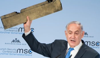Prime Minister Benjamin Netanyahu holding the piece of Iranian drone, at the Munich Security Conference, February 18, 2018.