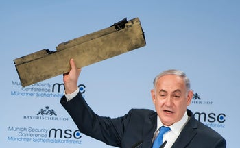 Prime Minister Benjamin Netanyahu holds what he claims is part of an Iranian drone shot down in Israeli airspace at the Munich Security Conference on February 18, 2018.