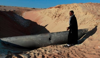 FILE PHOTO: A Bedouin man looks at a gas pipeline that was hit by a RPG in North Sinai March 6, 2012.