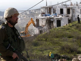 "Israeli soldiers and border police stand guard as Israeli hydraulic shovels demolish a Palestinian building north of the West Bank city of Hebron in the so-called ""Area C"" on February 14, 2018."