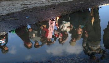 FILE PHOTO: A reflection of Syrian children is seen in a puddle of water in the Syrian rebel enclave of Eastern Ghouta on February 14, 2018.