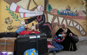 A woman and child wait for a travel permit to cross into Egypt through Gaza's Rafah border crossing after it was opened by Egyptian authorities for humanitarian cases. February 8, 2018