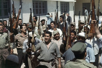 Palestinian Refugee Army recruits rally for war in the Gaza Strip in May 1967, raising their rifles and shouting, 'We want to fight. We will retake our homeland. Palestine is Arab.'