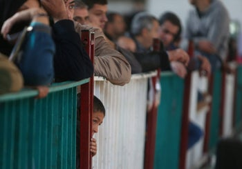 A Palestinian boy waits with his family for a travel permit to cross into Egypt through the Rafah border crossing in the southern Gaza Strip. December 17, 2017