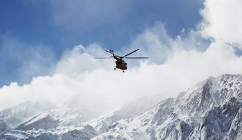 A rescue helicopter flies over the Dena mountains, Iran, searching for wreckage of a plane. February 19, 2018.