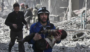 A Syrian civil defense member carries an injured child following government bombing in the rebel-held Eastern Ghouta region, Syria. February 19, 2018.