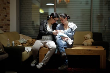 Adi (right) and Hela Maoz Ofir with their newborn baby.