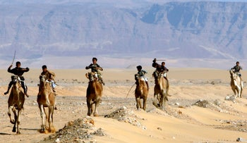 Bedouin children ride their camels during the Al Suez camel race in Ain Musa, 140 kilometers northwest of Cairo.