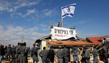 """An Israeli settler atop a building with an Israeli flag and a banner saying """"I'm at military reserve duty"""" in the West Bank settlement of Elazar, which is slated for demolition. November 29, 2017."""