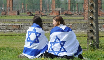 Two girls draped in Israeli flags sit in front of a barbed wire fence in the former German Nazi Death Camp Auschwitz-Birkenau during the yearly March of the Living, in Brzezinka, Poland, Thursday, May 5, 2016.
