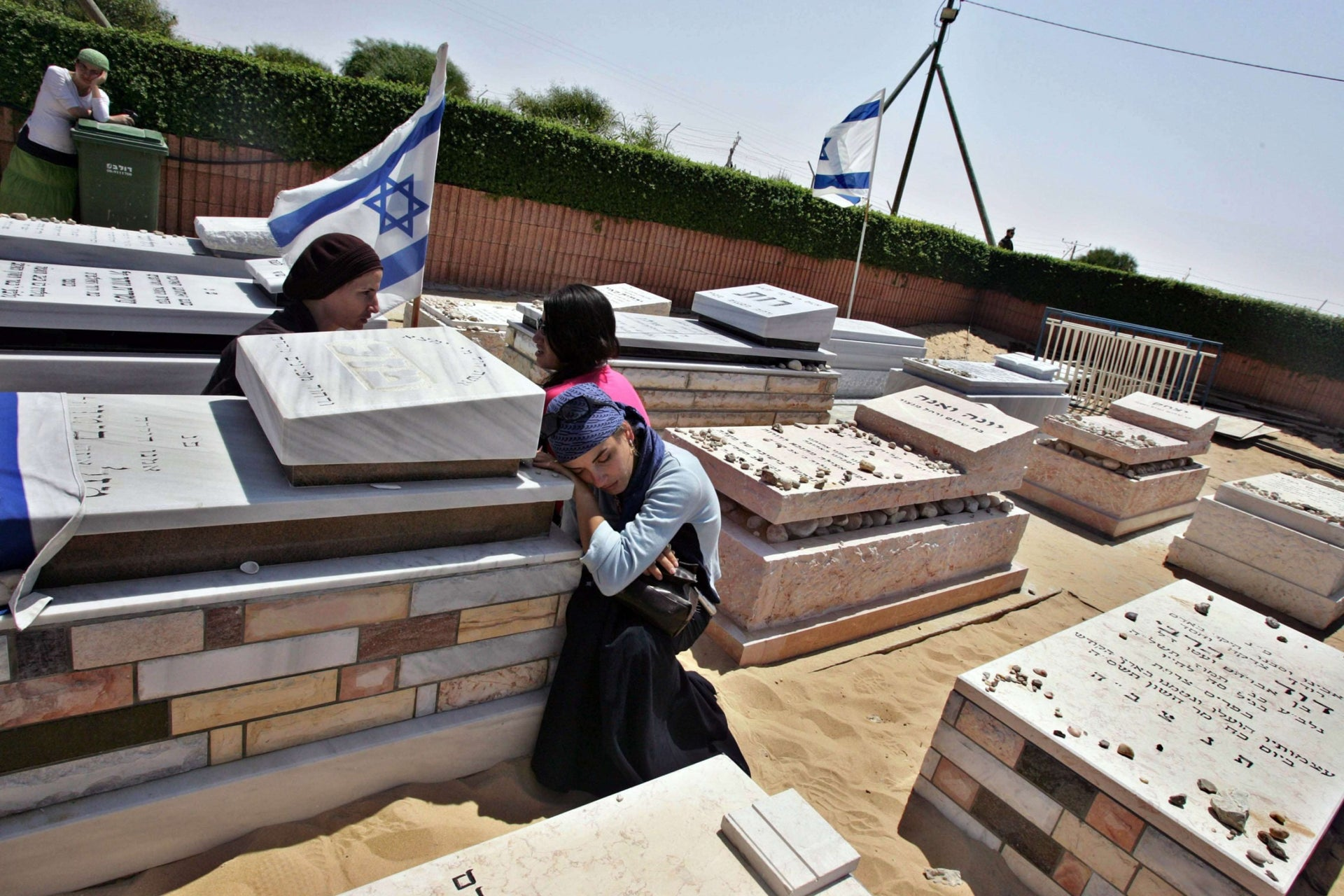 Israelis mourning next to the graves of relatives in the Gush Katif cemetery, before the exhumation of graves as part of Israel's disengagement from the Gaza Strip, August 2005.