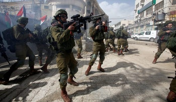 Israeli soldiers aim their weapons at Palestinian protesters during clashes in Hebron, West Bank, February 16, 2018.