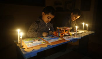 Palestinian children use candlelight to read books and draw due to electricity shortages in Gaza City on February 16, 2018.