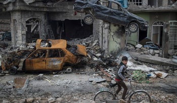 FILE PHOTO: A boy rides his bike past destroyed cars and houses in a neighborhood recently liberated by Iraqi security forces on the western side of Mosul, Iraq. Six African nations are among the 10 worst in the world to be a child in a war zone, according to a new report by Save the Children released Thursday, Feb. 15, 2018 that looks at factors including attacks on schools, child soldier recruitment, sexual violations, killings and lack of humanitarian access. (AP Photo/Felipe Dana, File)