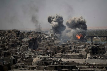 """FILE - In this July 11, 2017 file photo, airstrikes target Islamic State positions on the edge of the Old City a day after Iraq's prime minister declared """"total victory"""" in Mosul, Iraq."""