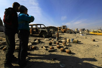 TOPSHOT - Syrian boys look at shells and undetonated mines lying on a street in Raqa that were left by the Islamic State (IS) group on January 16, 2018.