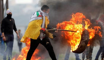 A Palestinian demonstrator moves a burning tire during clashes with Israeli troops near Nablus, in the occupied West Bank February 23, 2018.