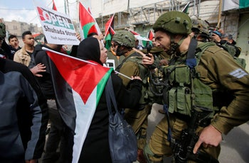 An Israeli soldier argues with a Palestinian demonstrator during clashes at a protest in Hebron, in the West Bank February 23, 2018.