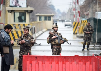 Afghan security personnel stand guard near the site of a suicide bombing in Kabul, February 24, 2018.