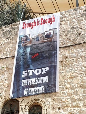 """A sign on the Church of Holy Sepulchre says """"enough is enough, stop the persecution of churches.'"""