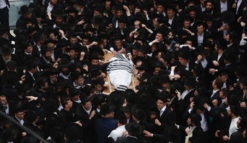 Ultra-Orthodox Jewish men mourn as they carry the body of Rabbi Shmuel Auerbach, head of an ultra-Orthodox Jewish denomination known as the Jerusalem Faction, during his funeral in Jerusalem February 25, 2018.