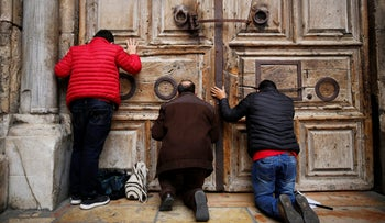 Worshippers kneel and pray in front of the closed doors of the Church of the Holy Sepulchre in Jerusalem's Old City, February 25, 2018.