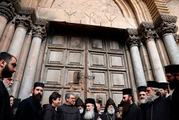 Christian leaders stand outside the closed doors of the Church of the Holy Sepulchre in Jerusalem's Old City, February 25, 2018.