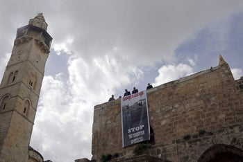A protest sign hangs outside of the Church of the Holy Sepulchre, in Jerusalem, February 25, 2018.