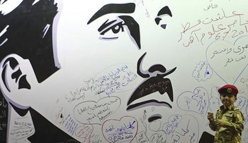 A young boy poses for a photo after writing a comment on a wall bearing a portrait of Qatar's Emir, Sheikh Tamim bin Hamad Al Thani,