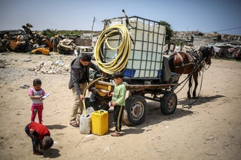 A man fills a bucket with water brought by a water tank carriage as Palestinians face a water crisis in Gaza City, Gaza on May 9, 2016.