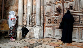 Two Christian women pray by the closed door of the main entrance of the shuttered Church of the Holy Sepulchre in Jerusalem, February 26, 2018.