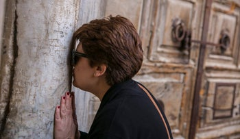 A pilgrim kisses the Church of the Holy Sepulchre in Jerusalem, February 26, 2018.