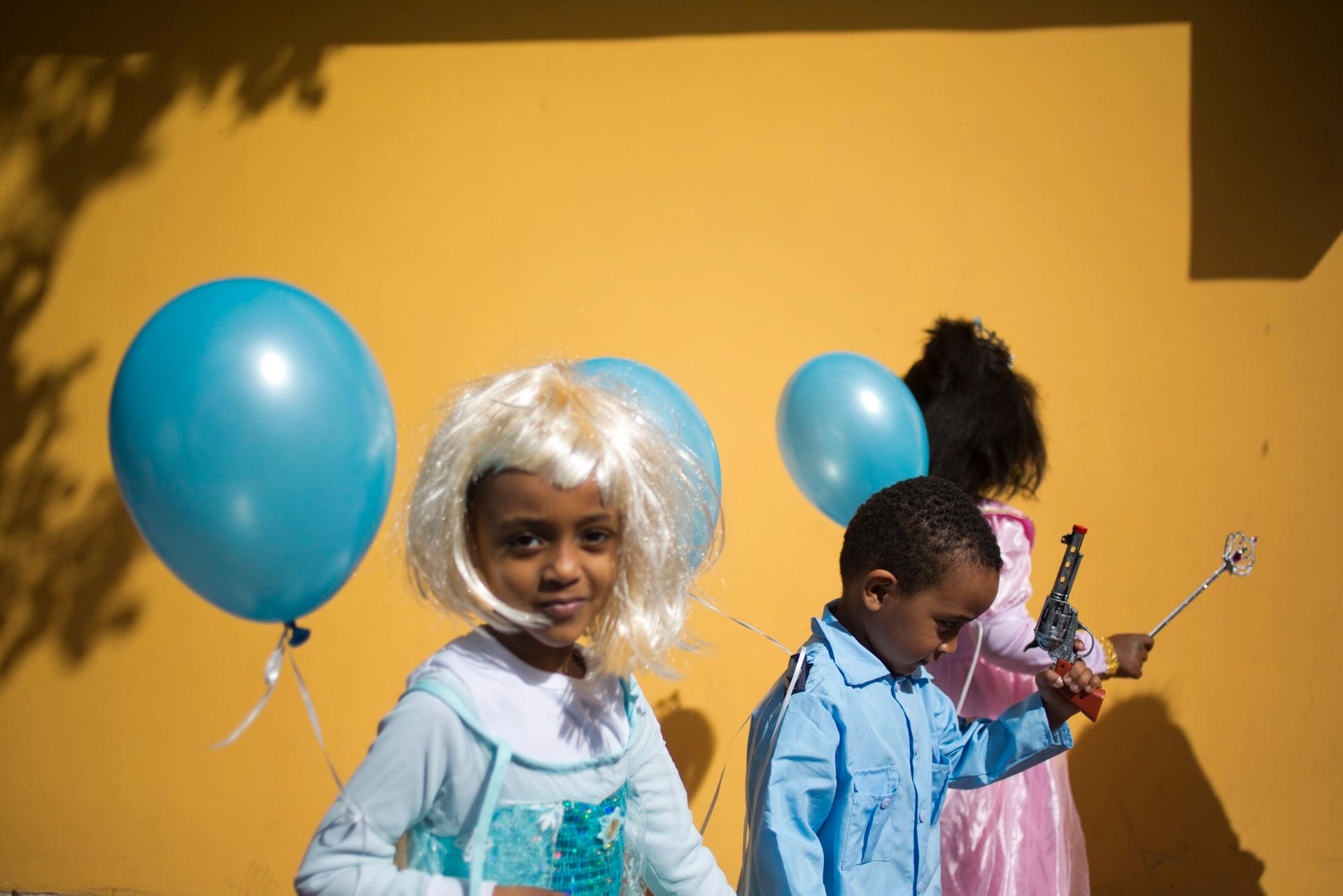 Children of asylum seekers, mostly from Eritrea and Sudan, wear costumes during the Purim parade festival in Tel Aviv, Tuesday, Feb. 27, 2018. The Jewish holiday of Purim commemorates the Jews' salvation from genocide in ancient Persia, as recounted in the Book of Esther, which is read in synagogues. Other customs include: sending food parcels and giving charity, dressing up in masks and costumes, eating a festive meal, and public celebrations.