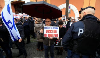 """A man from Israeli community of Rome holds a banner reading """"Denying the story means killing again"""" as he protests in front of the Polish embassy in Rome, Italy February 8, 2018."""