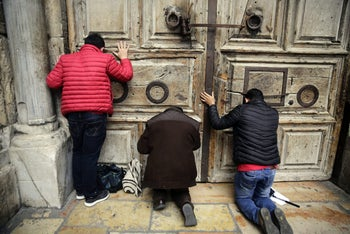 Christian visitors pray outside the shuttered Church of the Holy Sepulchre in Jerusalem, February 25, 2018.