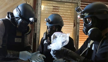FILE PHOTO: A UN chemical weapons expert, wearing a gas mask, holds a plastic bag containing samples from one of the sites of an alleged chemical weapons attack in the Ain Tarma neighbourhood of Damascus, Syria, August 29, 2013.