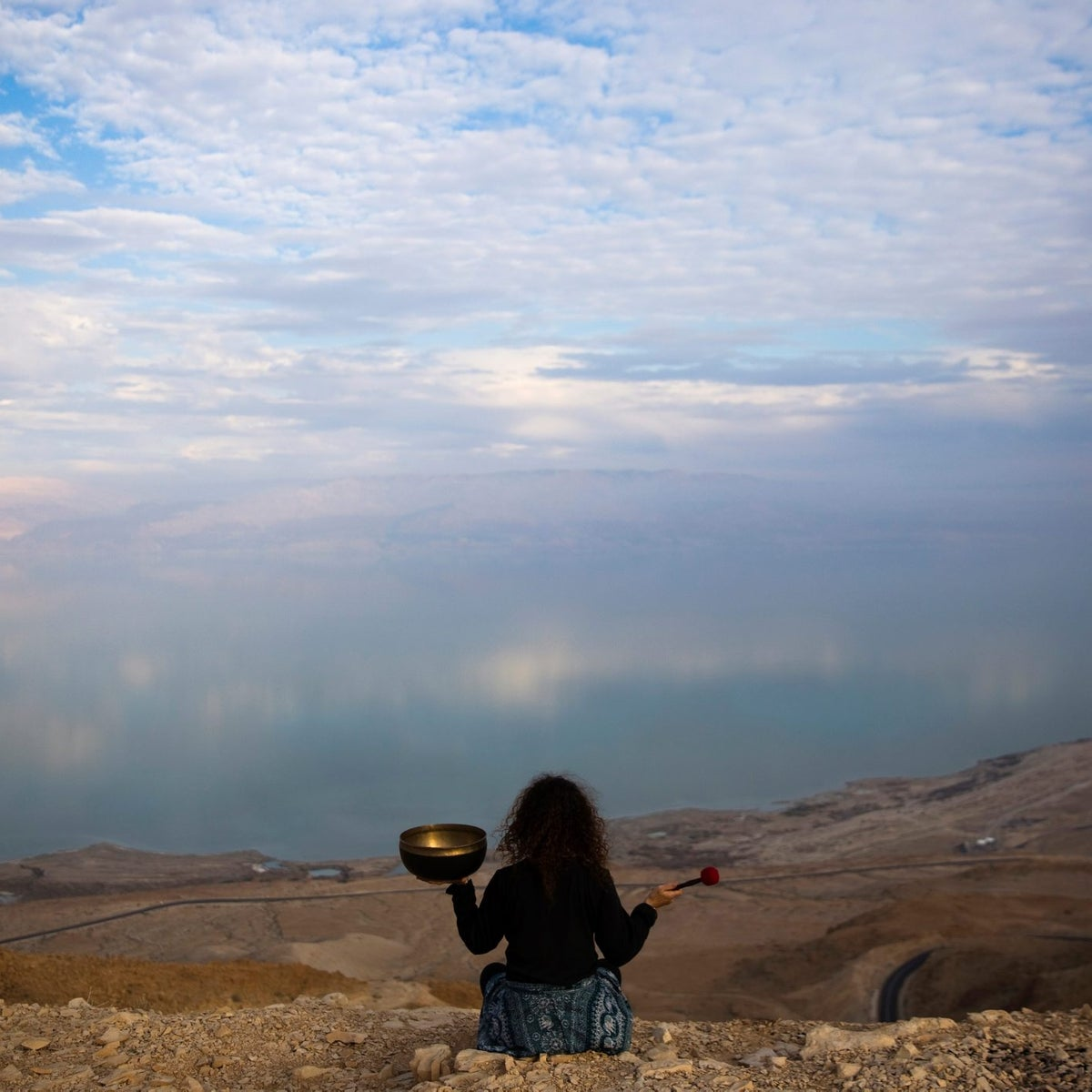 Jade holds a Tibetan singing bowl as she sits on a cliff overlooking the Dead Sea, February 20, 2018.