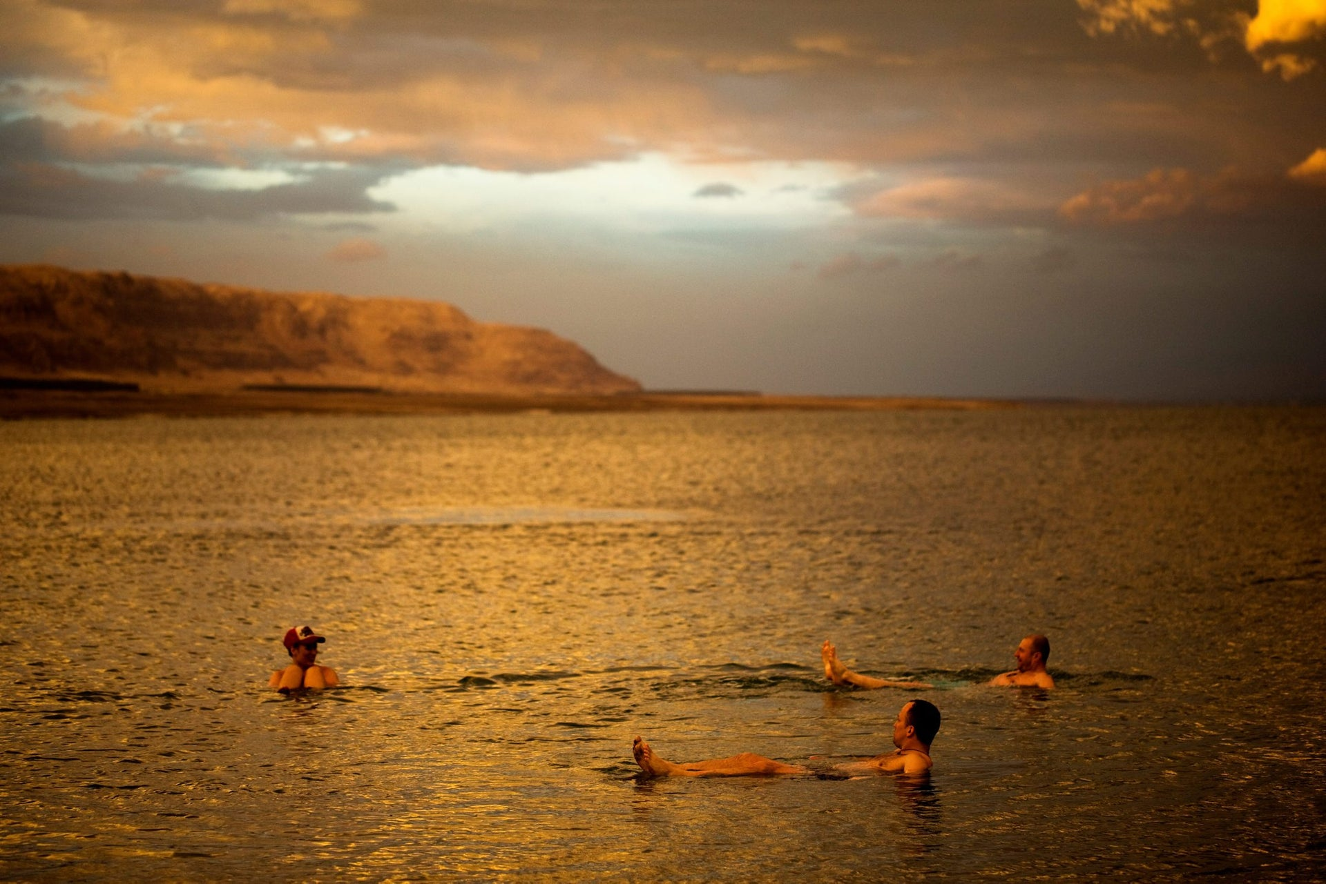 Tourists from Poland float in the Dead Sea during sunset, January 25, 2018.