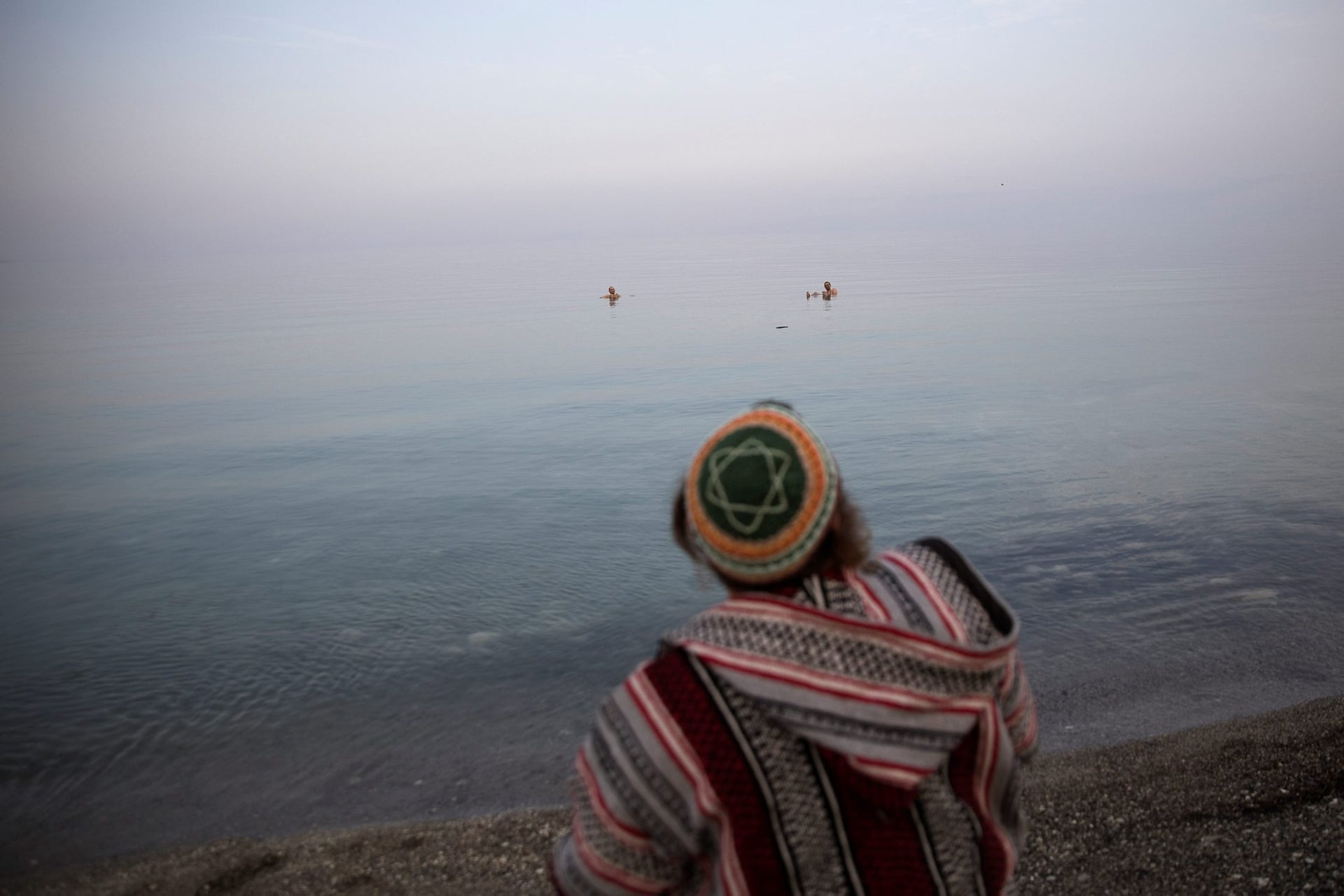 A man sits on the shore of the Dead Sea, near Metzoke Dragot in the Israeli occupied West Bank, February 7, 2018.