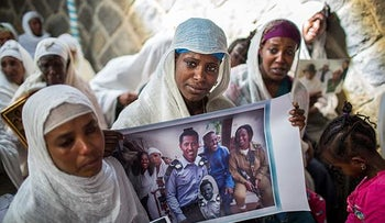 Members of Ethiopia's Jewish community hold pictures of their relatives in Israel, during a solidarity event at the synagogue in Addis Ababa, Ethiopia Wednesday, Feb. 28, 2018