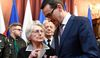 Anna Stupnicka-Bando, 89, a Polish woman recognized by Yad Vashem for saving Jews during the Holocaust, speaks to Polish Prime Minister Mateusz Morawiecki in Warsaw, February 26, 2018.