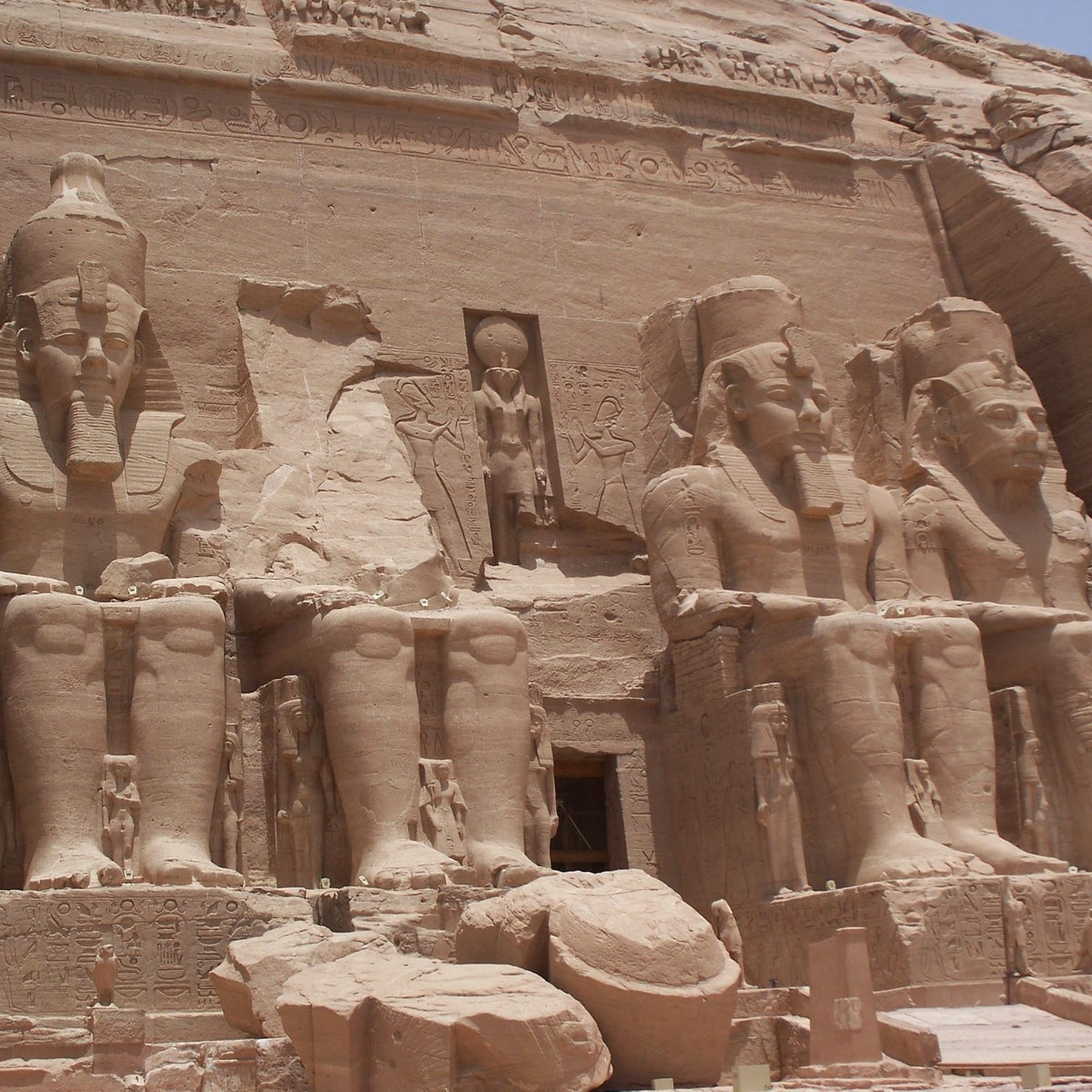 Temple of Ramesses II, 13th century B.C.E.: Photo shows four sitting pharaoh figures carved in stone, three quite complete from headdresses to feet and one missing everything from the hips up.