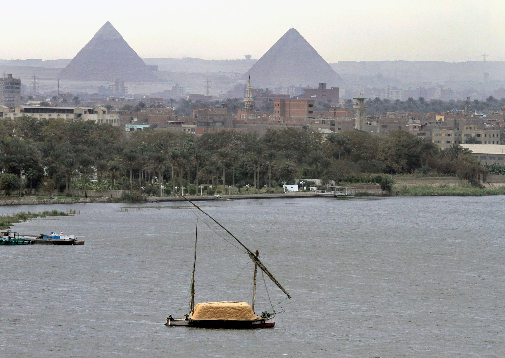 The Nile River, Cairo: A sailing boat carries a cargo of hay as it transits the Nile river passing the Pyramids of Giza in Cairo, Egypt