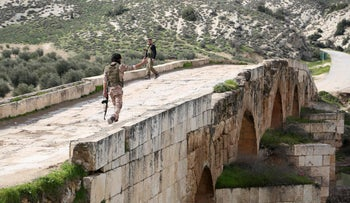 Turkish-backed Syrian opposition fighters walk on the Roman bridge northeast of the Syrian city of Afrin after taking control of it from the Kurdish People's Protection Units (YPG) on February 23, 2018