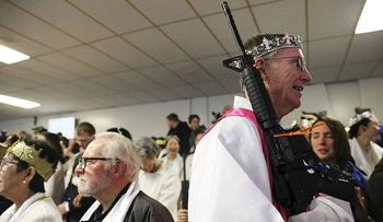 A church offical holds an AR-15 rifle during a ceremony at the World Peace and Unification Sanctuary in Newfoundland, Pennsylvania on February 28, 2018