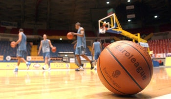 FILE PHOTO: A basketball of the Euroleague is seen on the floor as Maccabi Tel Aviv players practice in Tel Aviv, March 24, 2004.