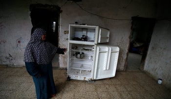 Palestinian woman Rawda Al-Waloud gestures as she stands next to a refrigerator inside her house in the northern Gaza Strip February 12, 2018. Picture taken February 12, 2018. REUTERS/Mohammed Salem