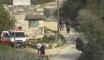 Palestinian couple flee Israeli forces in the West Bank village of Burin