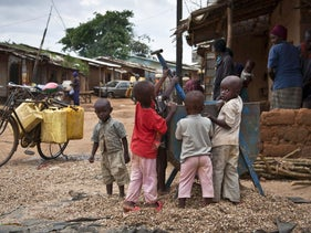 In this photo taken Tuesday, April 16, 2013, Rwandan refugee children play next to a nut processing machine on a street in the Nakivale refugee camp in Uganda.